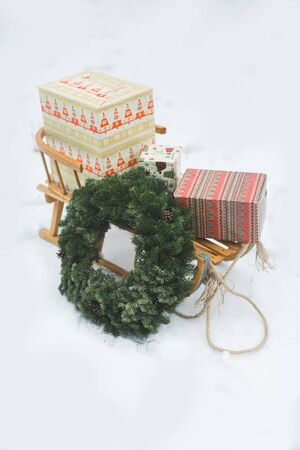 Christmas wreath and presents boxes on wooden sledge on white frosty snow background, winter time natural decor, new year and Christmas decorations and gifts Stok Fotoğraf