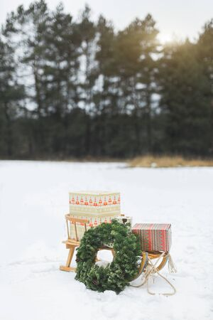 Beatiful wooden Santas sledge with Christmas gifts and wreath on the snow, over the background of frosty winter forest. Merry Christmas and Happy New Year Concept