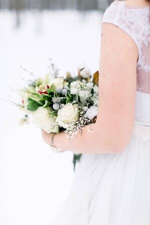 Wedding bouquet with flowers and cotton in hands of the bride. Winter time, snowy forest. Cropped image. Stok Fotoğraf