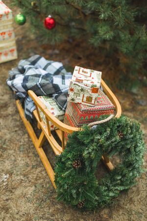 Beatiful wooden Santas sledge with Christmas gifts and wreath, over the background of winter forest and decorated Christmas tree. Merry Christmas and Happy New Year Concept