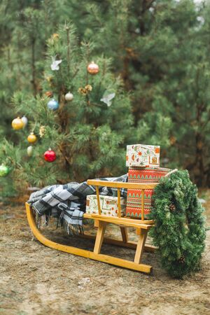 Christmas wreath and presents boxes on wooden sledge on the winter forest and Christmas trees background, winter time natural decor, new year and Christmas decorations and gifts