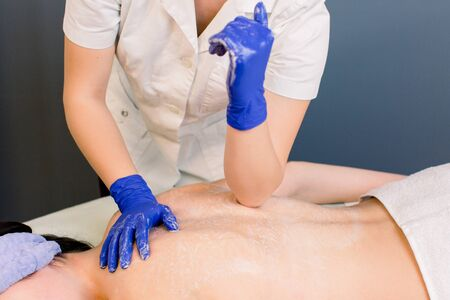 Professional back and body massaging to beautiful girl in cosmetology cabinet or beauty parlor. Hands of woman cosmetologist in blue gloves. Stok Fotoğraf