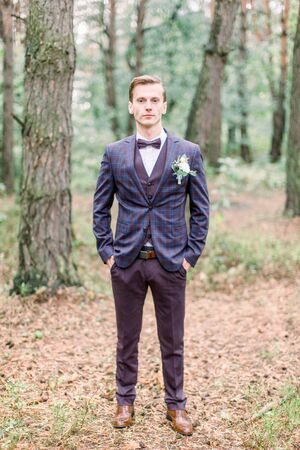 Ganzaufnahme des Bräutigams in Anzug und Fliege. Der hübsche elegante Bräutigam im karierten Anzug steht im Wald