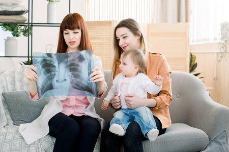 Doctor explaining chest xray image to mother with little daughter, sitting on the gray sofa in the clinic. Standard-Bild