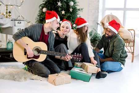 Picture showing group of four friends celebrating Christmas at home. Young Caucasian man is playing guitar and the girls and African man are smiling and singing carols.