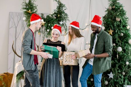 Group happy of friends laughing and sharing Christmas gifts in beautiful cozy studio Zdjęcie Seryjne