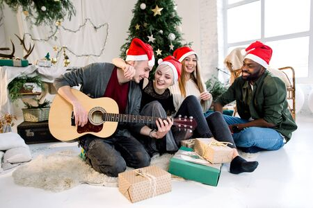 Cheerful young four international people celebrate Christmas and New Year together in cozy decorated studio. White man is playing guitar. Winter holidays concept