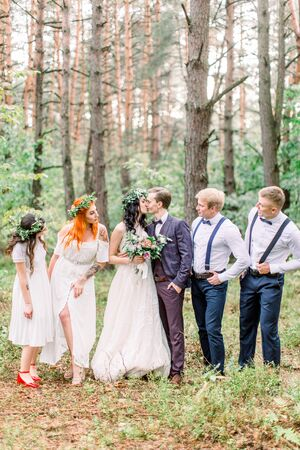 Beautiful kissing couple newlyweds with their friends having fun together. Happy bridesmaids and groomsmen with bride and groom on a walk in the forest