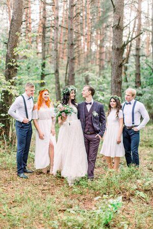 Bräutigam mit Braut und ihren Freunden. Rustikale Herbsthochzeit im Kiefernwald. Fröhliche Freunde. Hochzeitstag nach der Hochzeitszeremonie