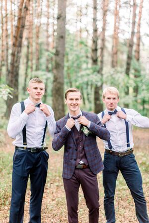 Groom is standing with his friends in the autumn wood. Young man in stylish elegant checkered suit and groomsmen at wedding photoshoot. Banque d'images
