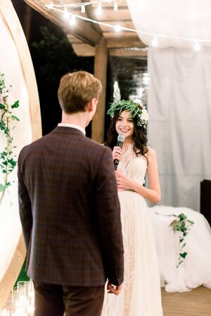 Pretty bride in wedding dress and floral wreath on head is speaking an oath to her groom during night wedding ceremony, standing near the rustic arch. Outdoors.