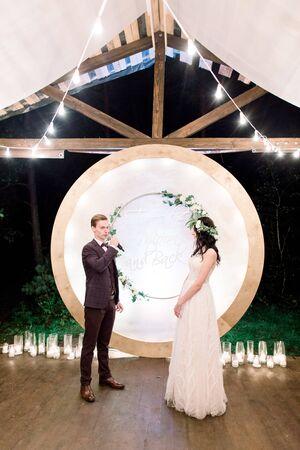 Nachthochzeitszeremonie im Freien. Braut und Bräutigam schwören sich auf Hochzeitsbogenhintergrund. Schönes frisch verheiratetes Paar. Rustikales Holzrestaurant mit Glühbirnen