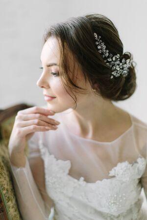 Retrato de belleza de una novia con una decoración exquisita en su cabello, foto de estudio en interiores. Foto de archivo