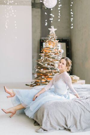 Pretty young woman in blue white dress sitting on the bed on the background of Christmas tree Foto de archivo