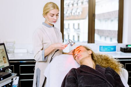 Light infrared therapy. Cosmetology face procedure. Beauty woman face. Young woman doctor beautician doing cosmetic facial skin rejuvenation for pretty young woman.