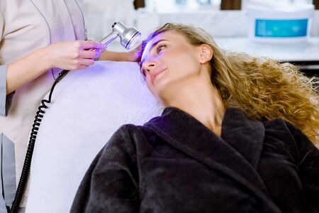 Light infrared therapy. Cosmetology head procedure. Close-up of beautiful woman face, receiving blue led light therapy. Cosmetic salon device. Facial skin rejuvenation