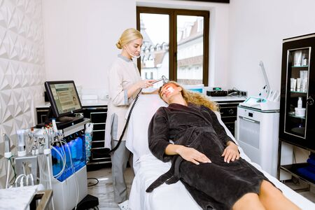 Woman doctor doing red led light therapy to young woman in beauty clinic, facial photo therapy for skin. Anti-aging treatments, photo rejuvenation procedure.