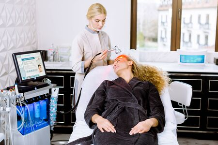 Facial beauty treatment in modern cometology clinic. Pretty blond curly woman having red led light therapy.
