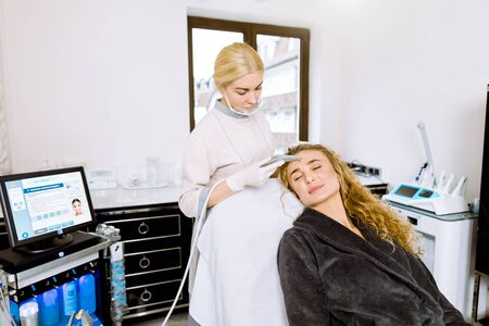 Young female doctor-cosmetologist makes the procedure microdermabrasion of the facial skin of a beautiful, young woman in cosmetology clinic. Professional skin care