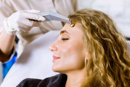 Beautiful blond woman getting facial microdermabrasion peeling treatment at luxury cosmetic beauty spa clinic. Exfoliation, rejuvenation and hydratation. Cosmetology concept