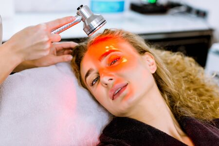 Anti-aging procedures. Skin care concept. Pretty blond woman receiving facial beauty treatment at modern cosmetic clinic. Red led light therapy. Rejuvenation, photo facial therapy