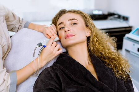 Face Skin Care. Close-up of pretty blond curly woman getting facial hydro microdermabrasion peeling treatment at cosmetology Spa Clinic. Hydra Vacuum Cleaner. Exfoliation, Rejuvenation, Hydratation. Stock Photo