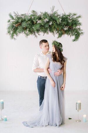 Ritratto di coppia felice isolato su sfondo bianco. Damigella d'onore in corona di pino e vestito blu grigio e ritratto del testimone dello sposo. Momento divertente del matrimonio.