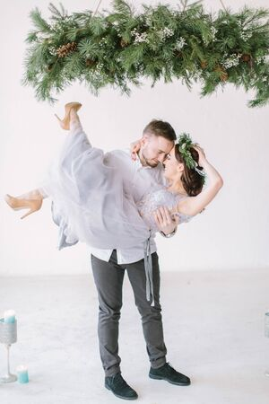 Beautiful bridesmaid in pine wreath and gray blue dress with handsome groomsman in the studio dancing.