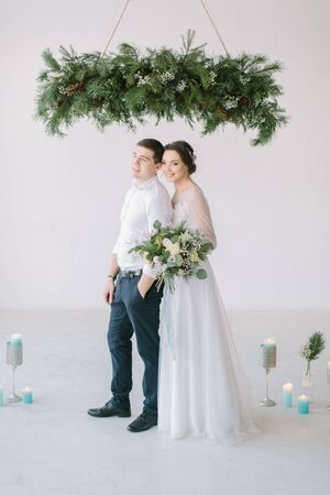 Very beautiful wedding of amazing couple. Wedding ceremony in light white room decorated with flowers and candles.