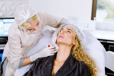 Young female doctor cosmetologist making injection in face and neck of young blond woman. Girl gets beauty facial injections in salon. Face aging, rejuvenation and hydration procedures Stock fotó