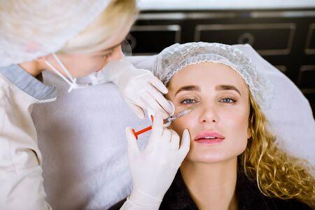Mooie vrouw krijgt injecties. Cosmetologie. Mooi gezicht. Close-up portret van blonde vrouw met vrouwelijke schoonheidsspecialist handen in de buurt van haar gezicht.