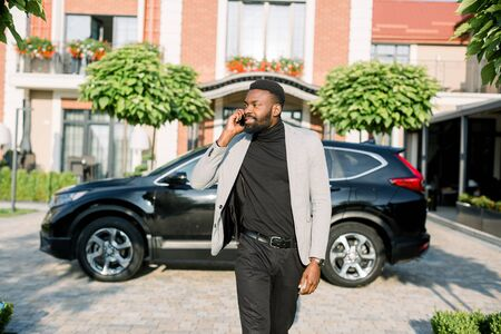 Serious rich African businessman in smart casual business suit talking over phone while walking on the yard and parking of modern business center. Black car crossover on the background.