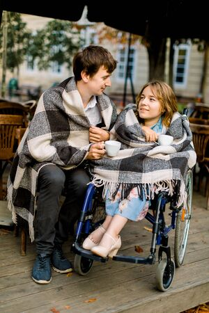 Attractive young woman on a wheelchair drinking coffee in a cafe outdoors with her husband and having a good time. Couple in wheelchair covered with checkered plaids outdoors.
