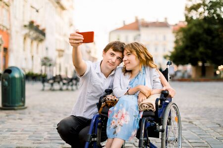 Happy couple in love taking selfie on the old city background - Disability concept with woman on wheelchair. Imagens