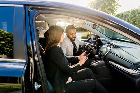 Giovane uomo afroamericano che comunica con una collega caucasica durante la guida in auto alla riunione di lavoro discutendo idee di avvio e presentazione da tablet digitale