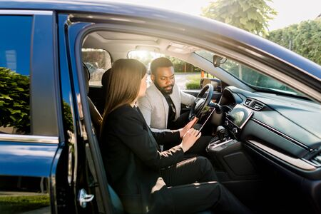 Młody Afroamerykanin komunikuje się z koleżanką rasy kaukaskiej podczas jazdy samochodem na spotkanie biznesowe, omawiając pomysły na start i prezentację z cyfrowego tabletu