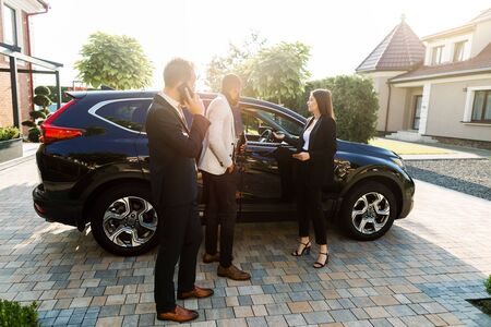 Two young multiracial businessmen, African and Caucasian, chosing a new car standing with salesperson, young pretty woman, in the car showroom outdoors. Side view.