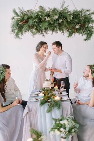 Bride and groom eating the wedding cake decorated with pine, berries and cotton flower with their bridesmaids and groommen Foto de archivo