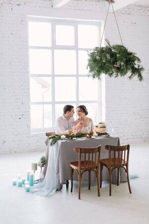Bride and groom posing at the decorated banquet table in the white hall. Hand in hands. Enjoy a moment of happiness and love. A series of photos in my portfolio. Wedding flowers on a table