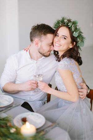 Pretty bridesmaid in pine wreath and groomman at the wedding table hugging and kissing. Group of people sitting at wedding table in the white hall decorated with pine, flowers and candles