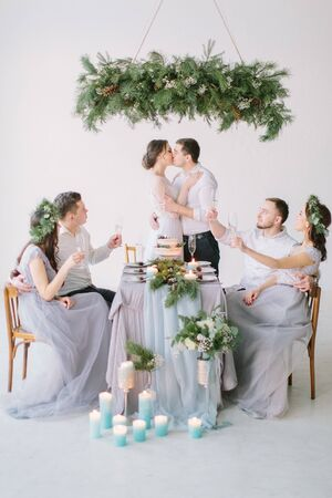 Wedding couple kissing at the decorated wedding table. Bridesmaids and groommen drink champagne sitting at the table in white studio