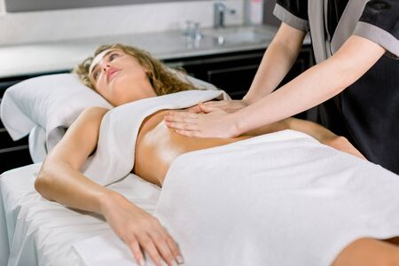 Side angle view of hands massaging female abdomen. Therapist applying pressure on belly. Pretty young blond woman receiving manual massage at spa salon Banco de Imagens