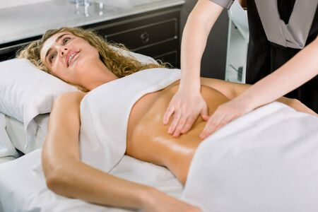 Beautiful blond curly woman smiling, while lying on the bed and having stomach massage. Body care, medical spa center.