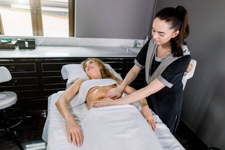Beautiful young woman having belly massage in modern medical and cosmetology center. Pretty female massage therapist massaging woman abdomen