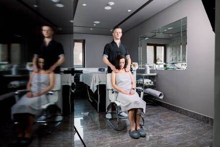 Young beautiful dark-haired woman is being massaged by young male therapist. Young man therapist doing back and neck massage to a woman sitting on the chair in the spa center