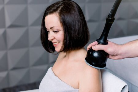 Side view of young smiling woman getting electric massage on her shoulders and neck in the spa. Hardware cosmetology, professional massage equipment. Close-up, hand of therapist holding device.