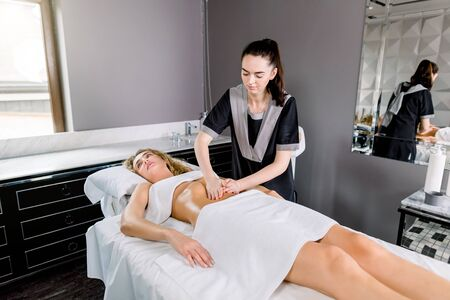 Beautiful young woman having visceral massage in spa center. Young female doctor therapist doing manual massage on female abdomen.