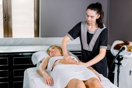 Beautiful young woman doctor massage therapist in a cosmetology room doing an abdomen massage to young blond woman