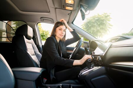 Side view of young beautiful business woman sitting in her car on driver seat and looking at camera. Sunny day. Business woman in car