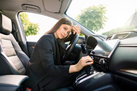 Side view of young pretty business lady in smart casual wear sitting in drivers seat in her car.